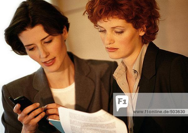 Zwei Geschäftsfrauen nebeneinander  eine mit Blick auf das Handy