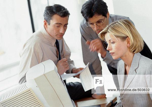Zwei Geschäftsleute prüfen Dokument  Geschäftsfrau betrachtet Computer