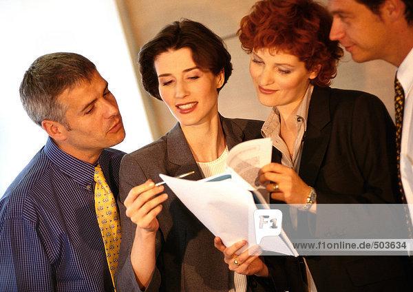 Vier Geschäftsleute bei der Prüfung von Dokumenten