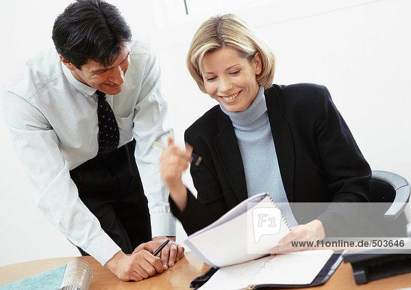 Geschäftsmann und Geschäftsfrau beim Betrachten des Dokuments