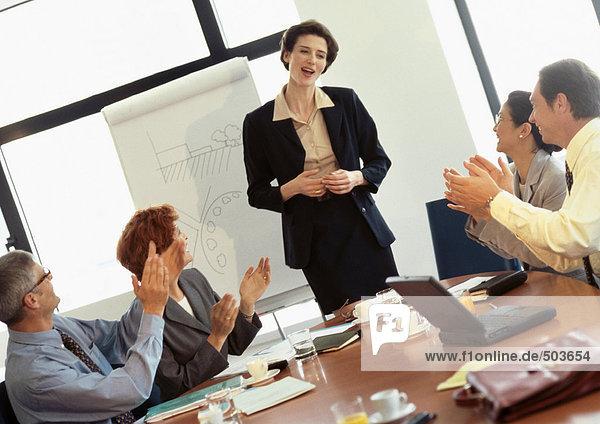 Gruppe von Geschäftsleuten im Konferenzraum  Geschäftsfrau wird applaudiert