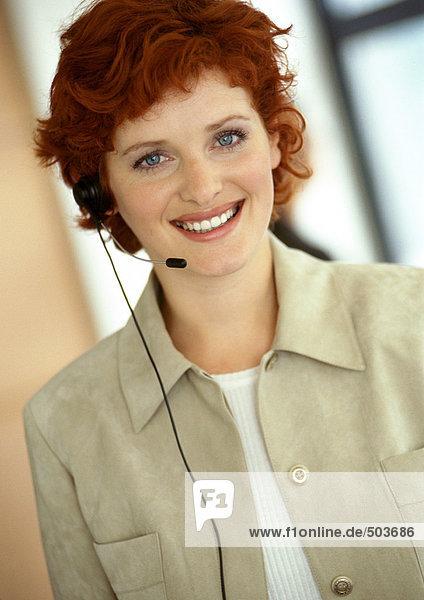 Geschäftsfrau mit Headset  Kamera lächelnd  Portrait