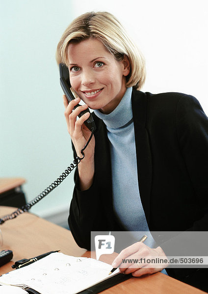 Businesswoman using telephone  smiling at camera  portrait