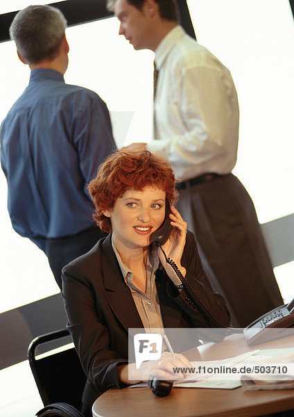 Geschäftsfrau sitzend  telefonierend  zwei Geschäftsleute im Hintergrund