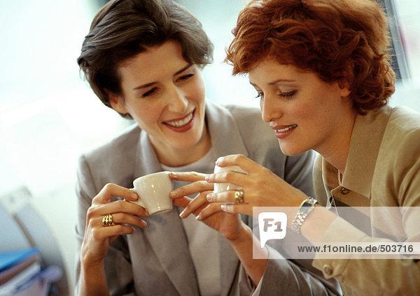 Zwei Geschäftsfrauen Seite an Seite  die Kaffeetassen halten
