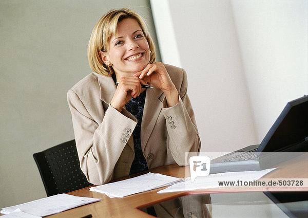 Geschäftsfrau am Schreibtisch sitzend  Hände unter dem Kinn  lächelnd