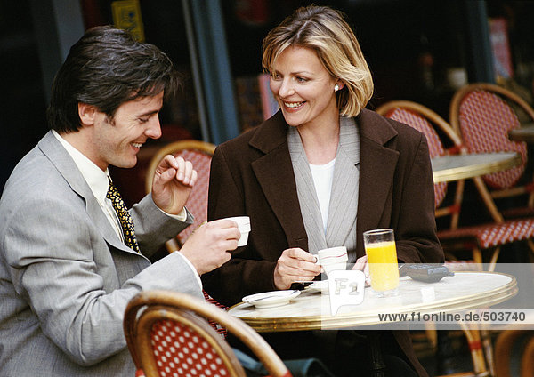 Geschäftsmann und Geschäftsfrau beim Kaffeetrinken auf der Caféterrasse