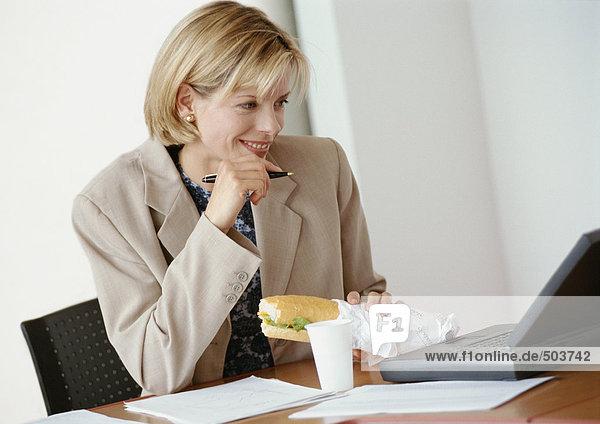 Geschäftsfrau am Schreibtisch sitzend mit Laptop-Computer  Sandwich haltend