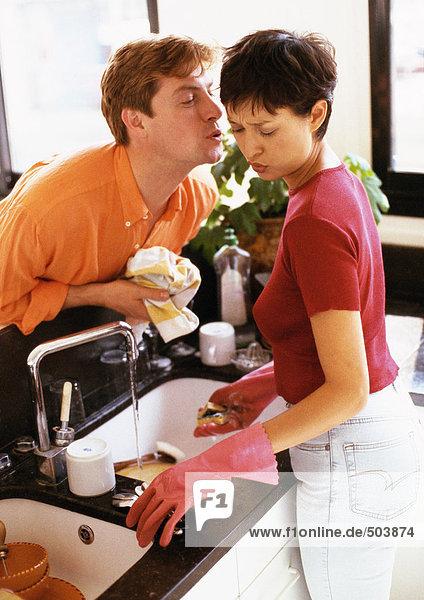 Frau wäscht Geschirr  Mann lehnt sich über den Tresen  um sie zu küssen.