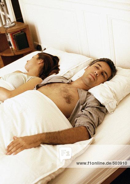 Im Bett liegendes Paar mit gegenläufig gedrehten Köpfen