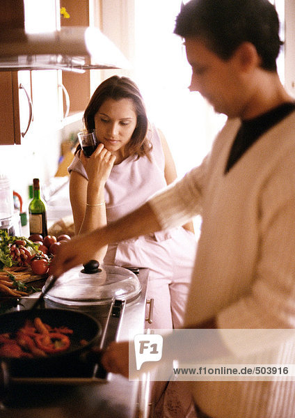 Man cooking in blurred foreground  woman holding glass in background