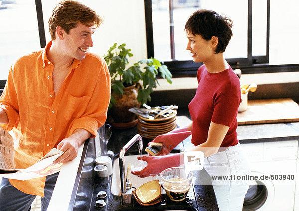 Mann und Frau in der Küche  schauen sich über den Tresen an  Frau beim Geschirrspülen