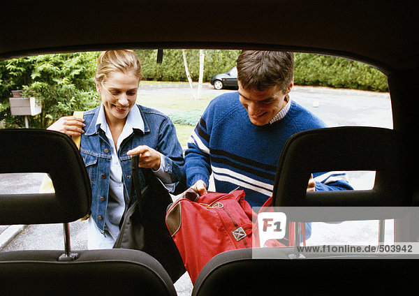 Mann und Frau legen Taschen in den Kofferraum  Kopfstützen im Vordergrund