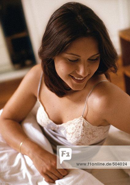 Frau im Bett sitzend