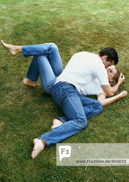 Paar auf Gras liegend  Mann lehnt sich über Frau