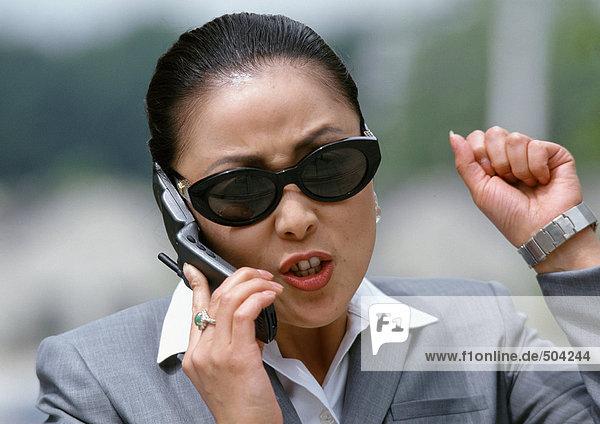 Geschäftsfrau am Handy  aggressiv gestikulierend