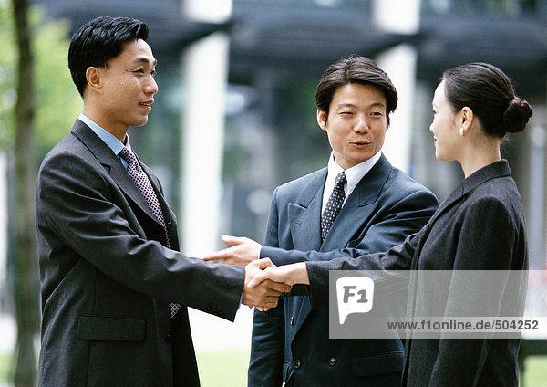 Mann und Frau beim Händeschütteln  der andere Mann stellt sie vor.
