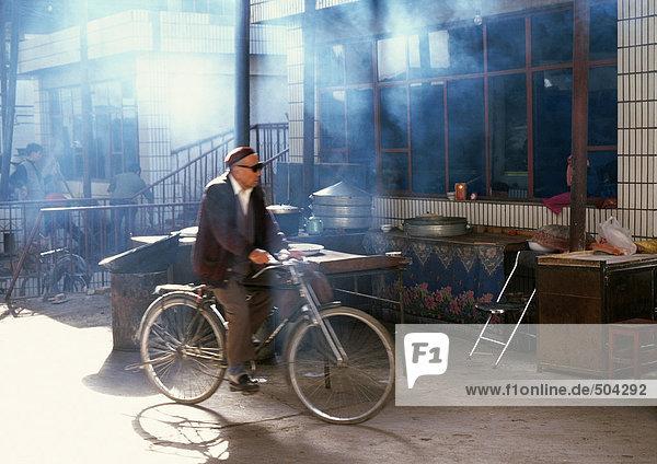 China  Provinz Xinjiang  Turpan  Mann auf dem Fahrrad in der Nähe der Ladenfront
