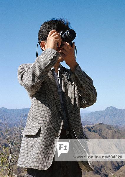 Mann mit Kamera  Berge im Hintergrund