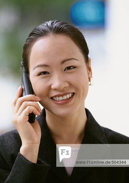 Frau mit Handy  lächelt in die Kamera  Porträt