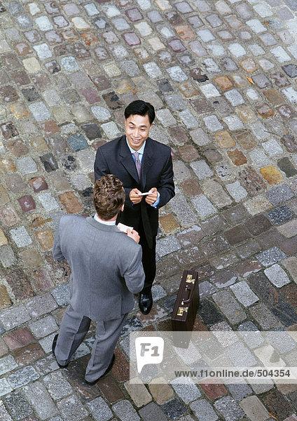 Zwei Männer stehen von Angesicht zu Angesicht auf Kopfsteinpflaster  erhöhte Ansicht