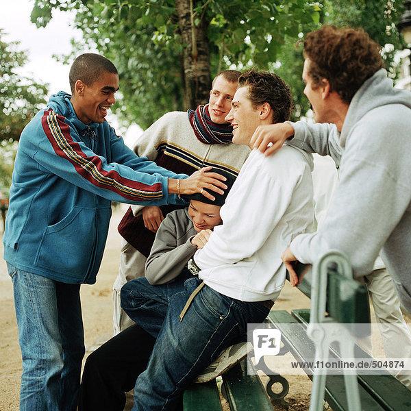 Jugendliche um die Parkbank gruppiert