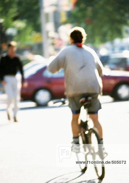 Fahrradperson in der Straße  Rückansicht