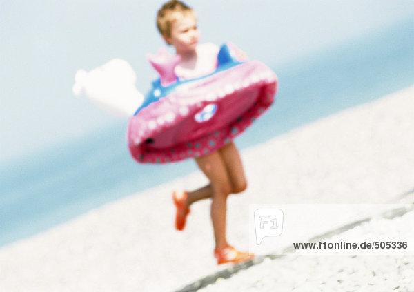 Kind läuft mit Schlauch am Strand  verschwommen