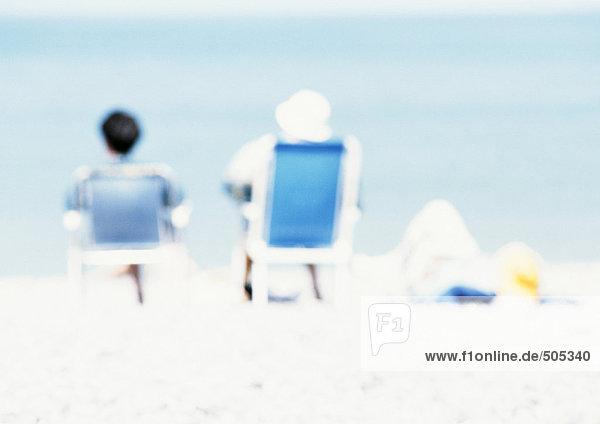 Paar auf Stühlen am Strand sitzend  Rückansicht  verwischt