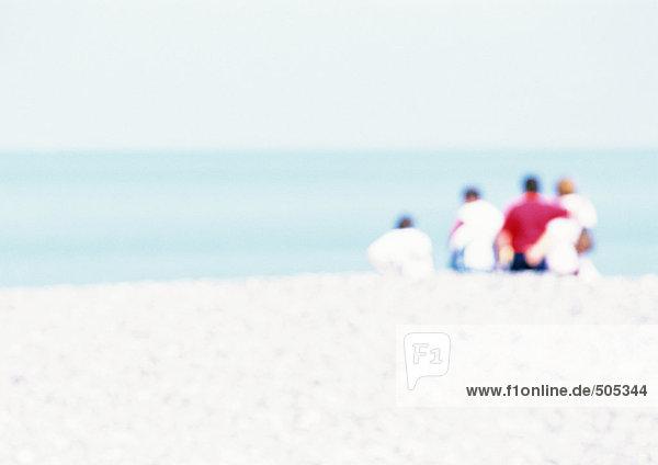 Gruppe von Menschen  die auf Sand am Strand sitzen  Rückansicht  unscharf