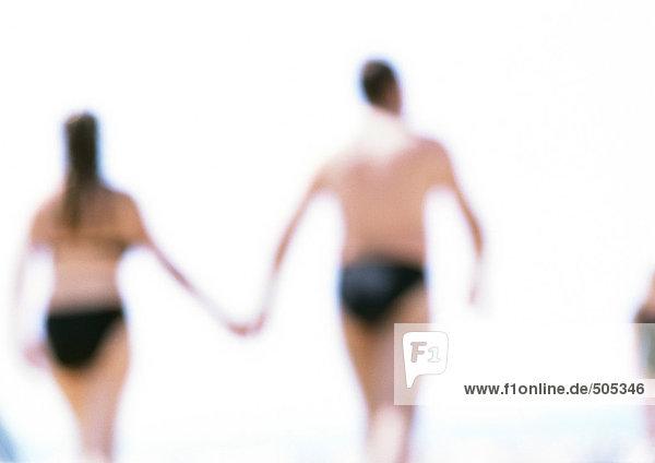 Mann und Frau halten Hände am Strand  Rückansicht  verschwommen in der Ferne.