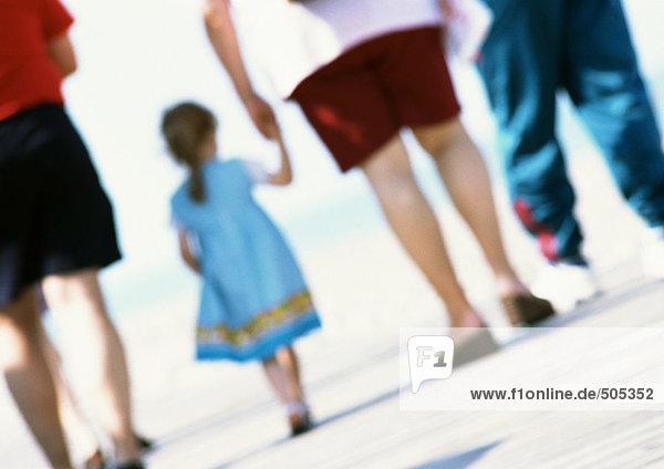 Gruppe von Menschen  die zusammen am Strand spazieren gehen  Nahaufnahme  verschwommen.
