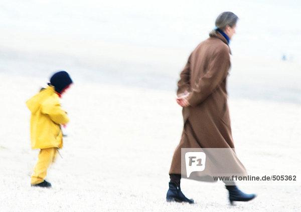 Frau und Kind in Mänteln  die am Strand spazieren gehen  verschwommen