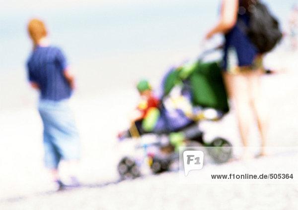 Menschen mit Kinderwagen am Strand  verwischt