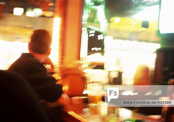 Leute sitzen am Tisch im Restaurant  helle Lichter im Hintergrund  verschwommen.