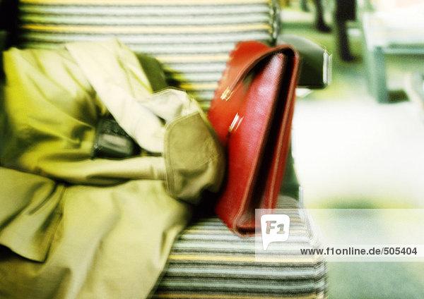 Mantel und Geldbörse auf dem Sitz  verschwommen