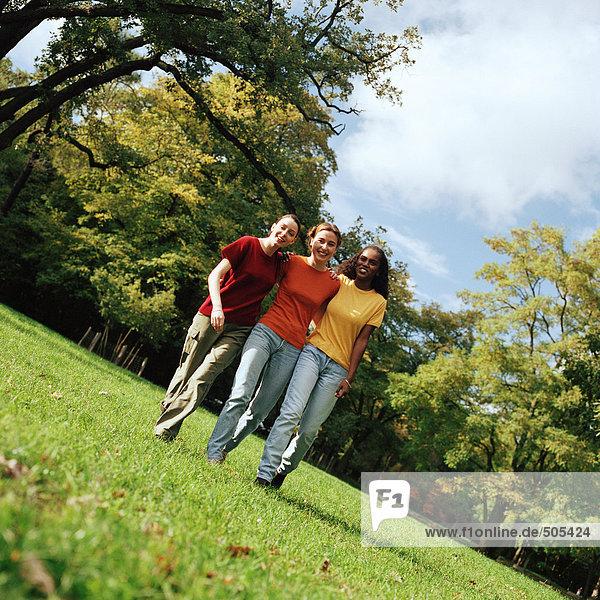 Drei junge Frauen  die auf Gras gehen  mit den Armen umeinander  Vorderansicht  volle Länge