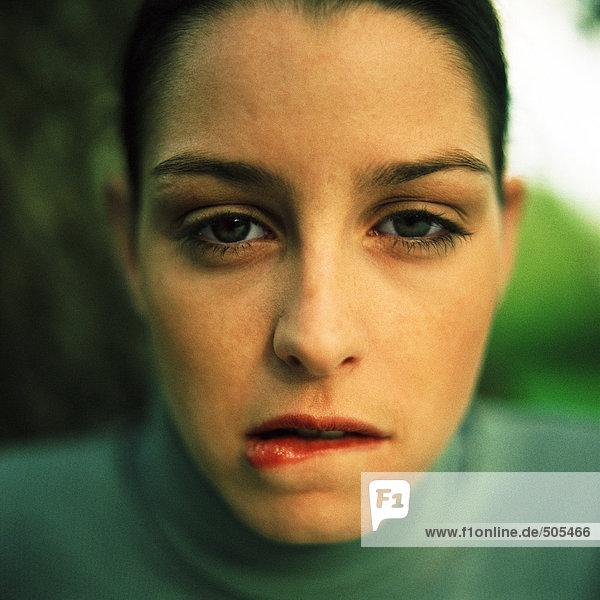 Junge Frau beißt die Unterlippe  schaut in die Kamera  Nahaufnahme  Porträt.