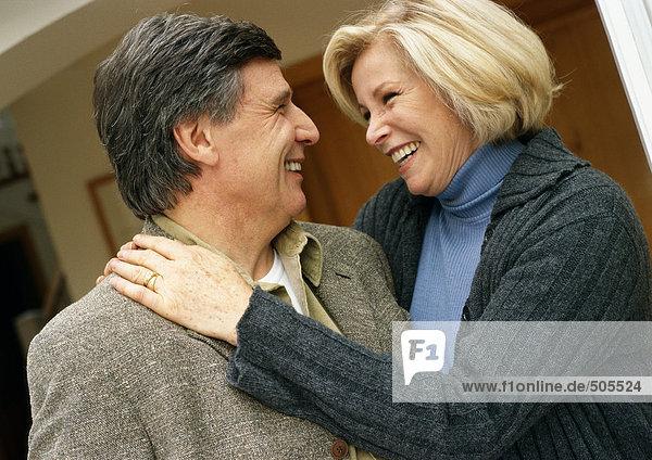 Mann und Frau lächeln von Angesicht zu Angesicht  Frau mit Armen um den Mann  Kopf und Schultern  Nahaufnahme