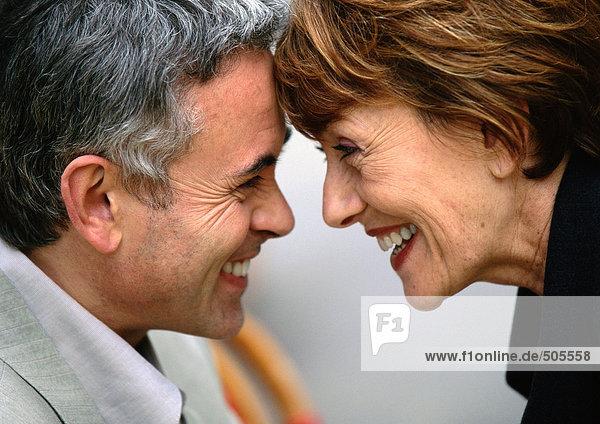 Reife Männer und Frauen sehen sich an und berühren sich lächelnd die Stirn.