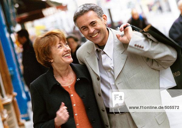 Mann und Frau gehen zusammen  Mann hält Einkaufstasche über die Schulter