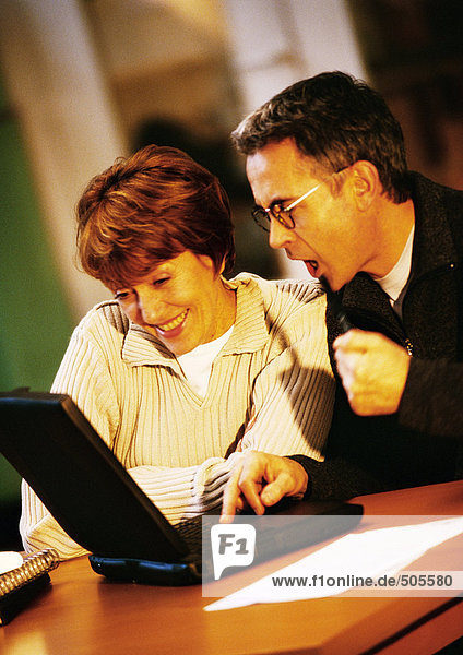 Man and woman sitting at table looking at laptop computer together