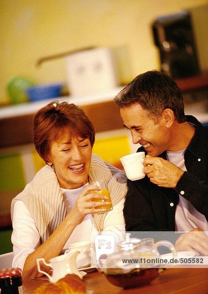 Mann und Frau beim Frühstücken am Tisch sitzend  lächelnd