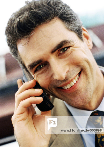 Businessman using cellular phone  smiling at camera  close-up  portrait.