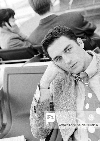 Geschäftsmann sitzt in der Flughafenlounge  schwarz-weiß.