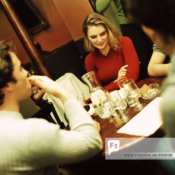 Group of young people sitting at table  drinking