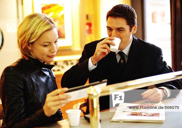 Geschäftsmann und Geschäftsfrau sitzen zusammen am Schalter und schauen auf das Ticket.