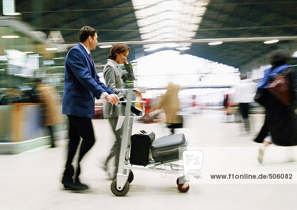 Geschäftsmann und Geschäftsfrau gehen zusammen mit Gepäck durch den Bahnhof  verschwommen.