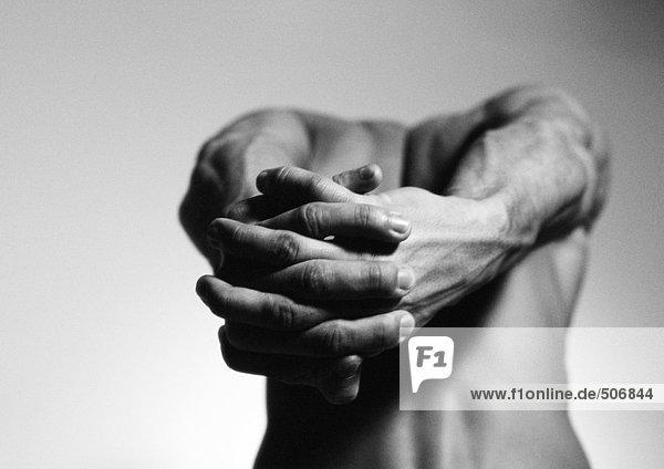 Nackter Mann  der die Arme hinter dem Rücken streckt  die Hände im Vordergrund zusammengehalten  schwarz-weiß. Nackter Mann, der die Arme hinter dem Rücken streckt, die Hände im Vordergrund zusammengehalten, schwarz-weiß.