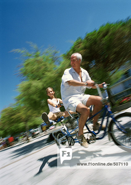 Mature man and girl riding tandem bike  granddaughter with legs out  blurred motion
